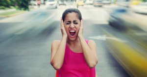 Woman standing in middle of road with hands over ears and mouth open in scream