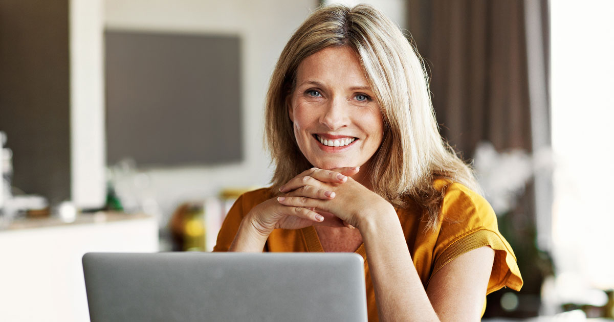 Woman smiling with hands folded under chin in front of laptop