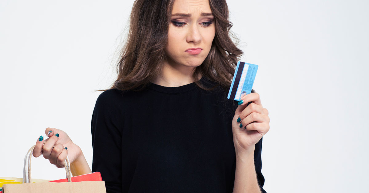 Woman holding a shopping bag and looking at credit card