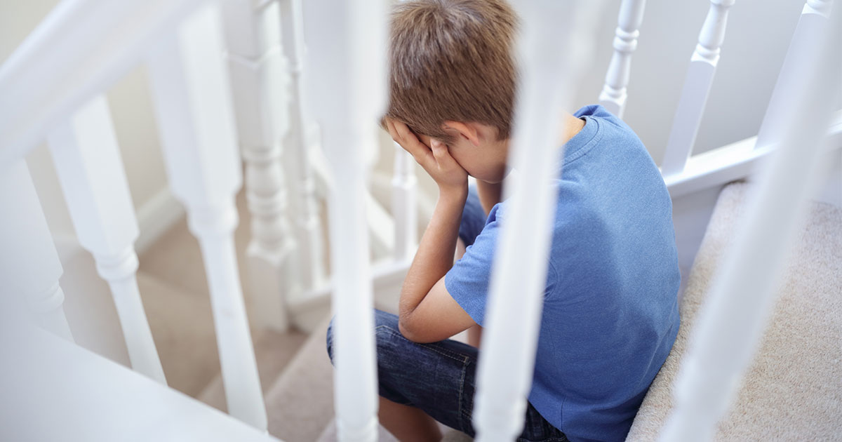 Young boy sitting on stairs looking angry