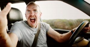 Man yelling while behind steering wheel of car