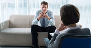 Man sitting on couch, facing therapist