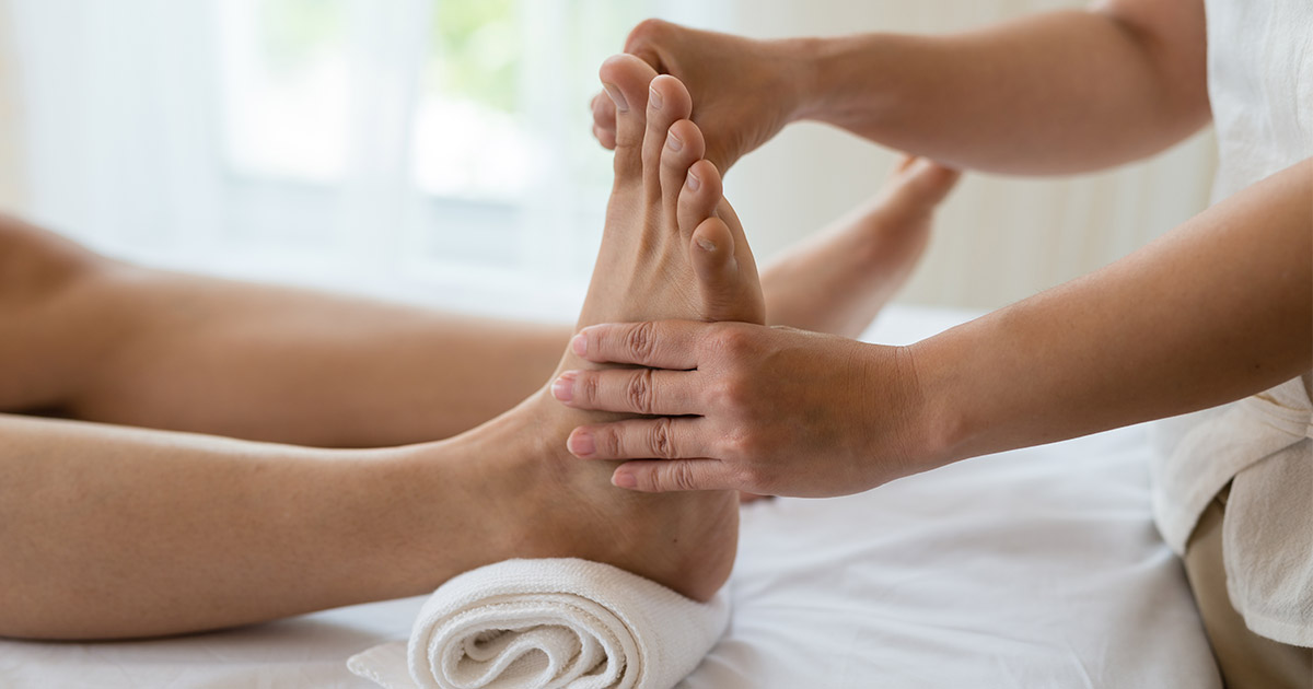 Person having reflexology conducted on the bottom of their foot