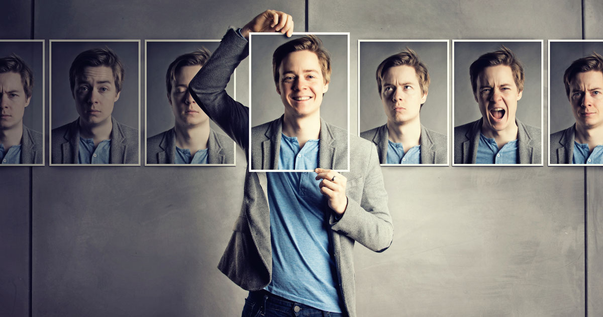 Someone holding a photo of their face with a line of other photos of his face displaying different emotions