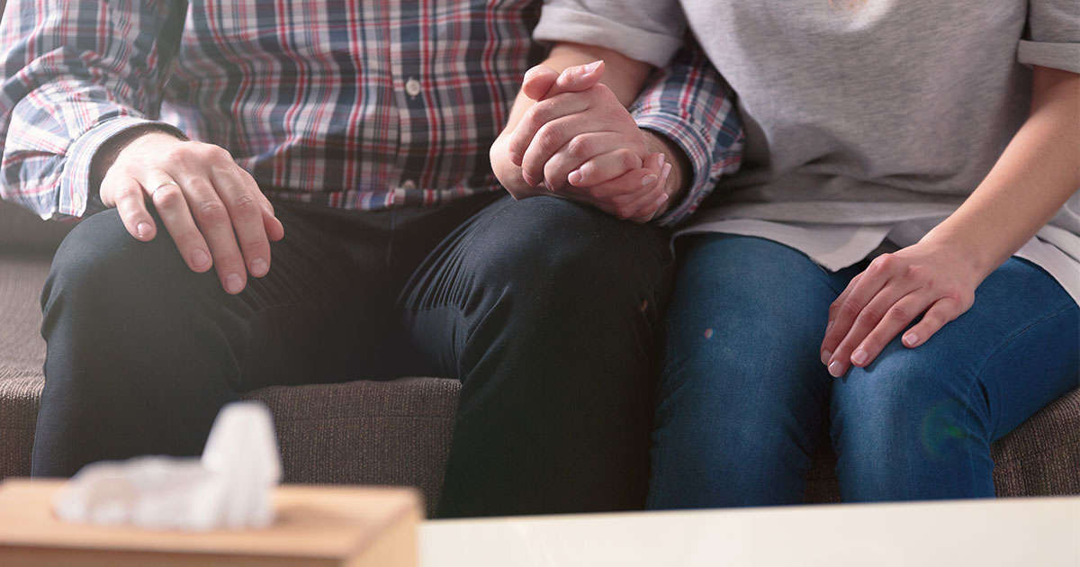 Two people sitting on couch holding hands