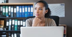 Woman looking thoughtful as sitting in front of laptop