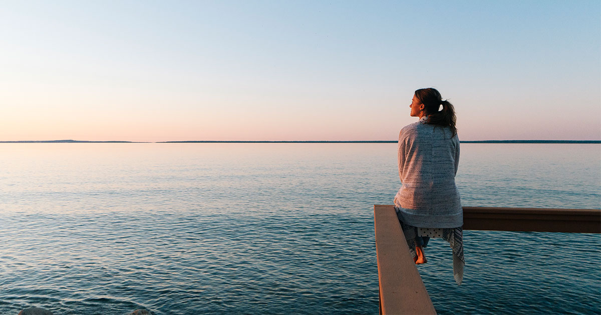 Woman sitting on railing next to the water