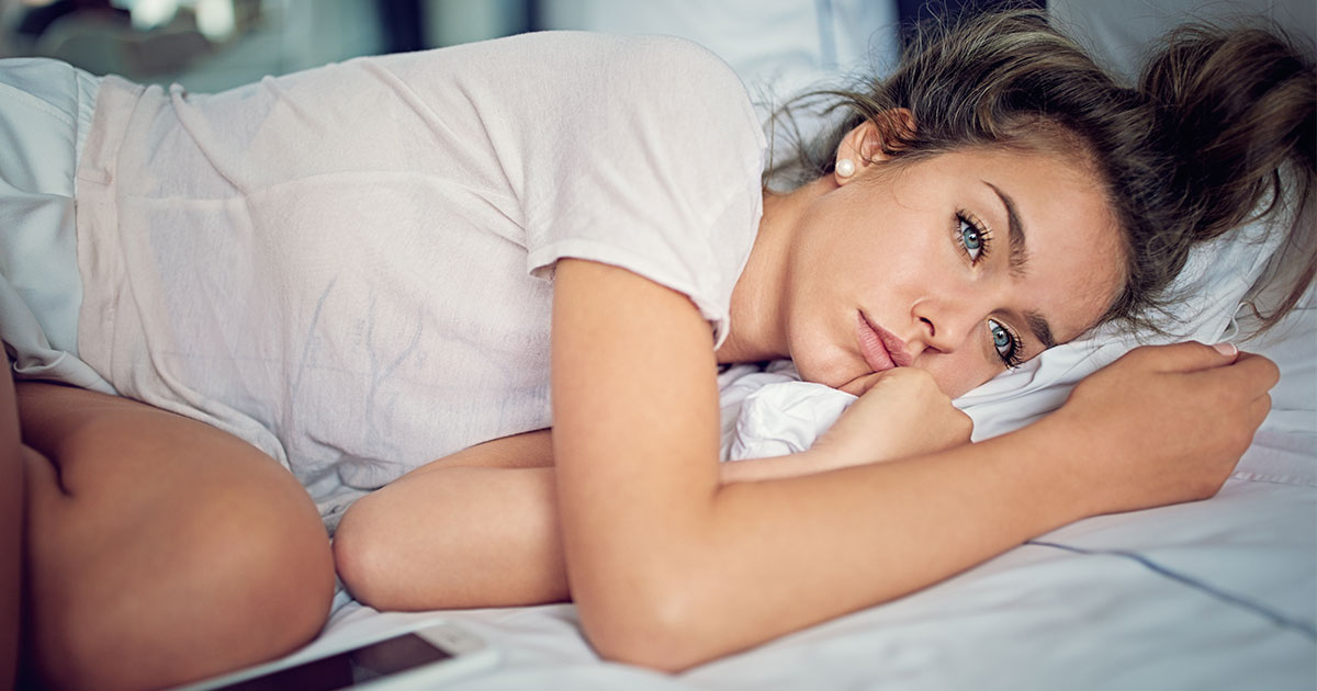 Woman laying on bed, looking sad