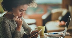Woman looking at phone as she sits in front of laptop
