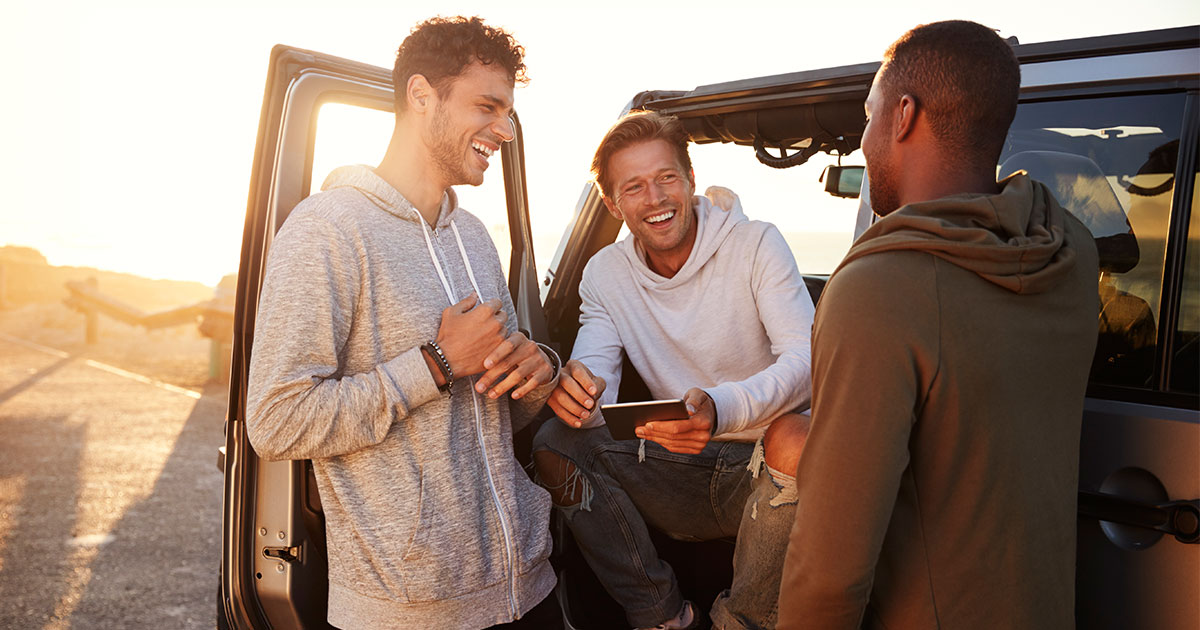 Three guys hanging out outside of a truck