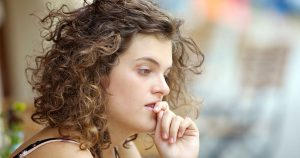 Woman looking sad, hand pressed to mouth