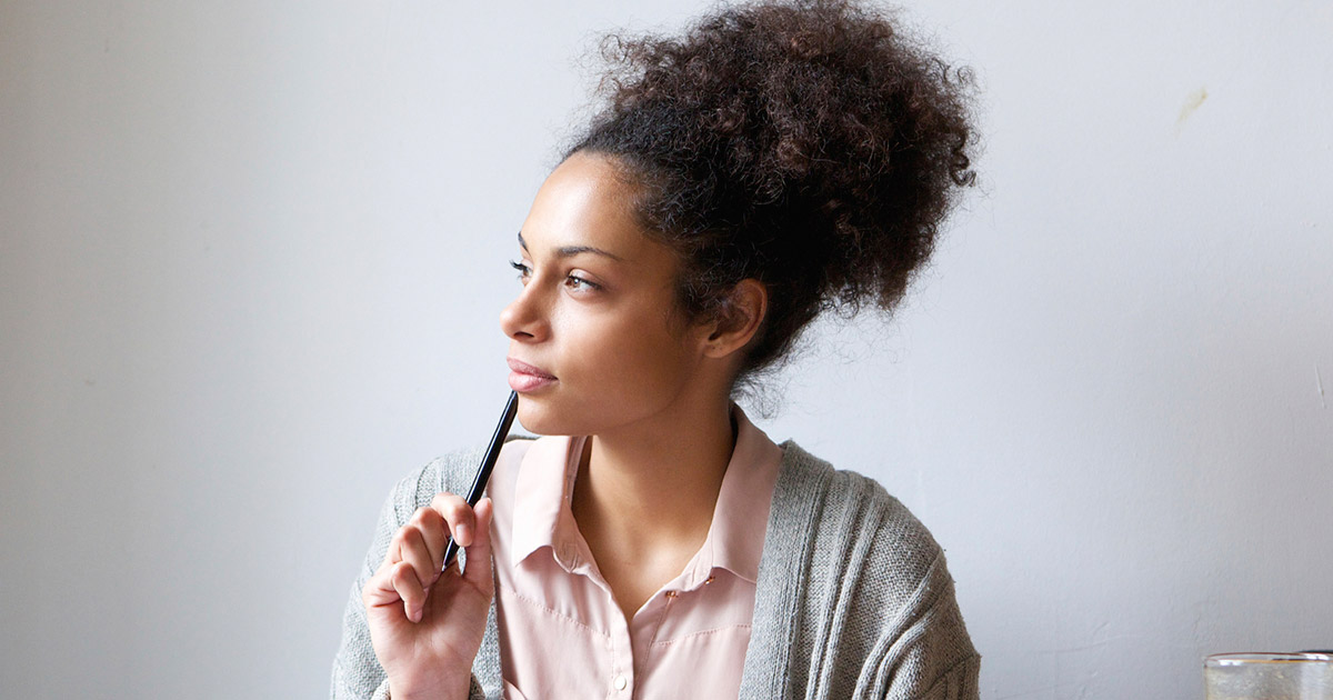 Woman looking thoughtful with pen held to chin