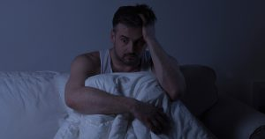 Man sitting in dark in bed, wide awake