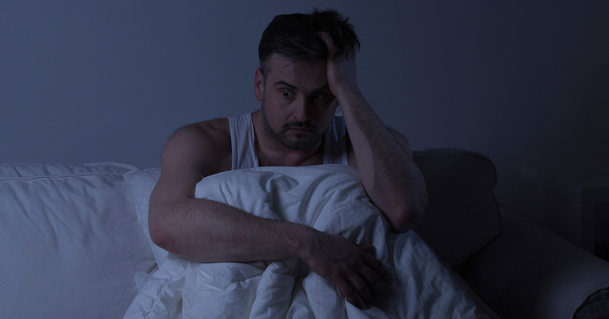 Man sitting in dark in bed, wide awake