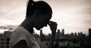 Woman standing outside with fingers pinching bridge of nose