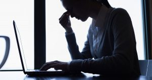 Woman sitting at laptop with fingers pinching nose
