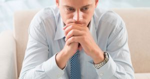Man looking contemplative with chin resting on folded hands