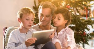 Dad sitting with two kids in front of Christmas tree, looking at tablet