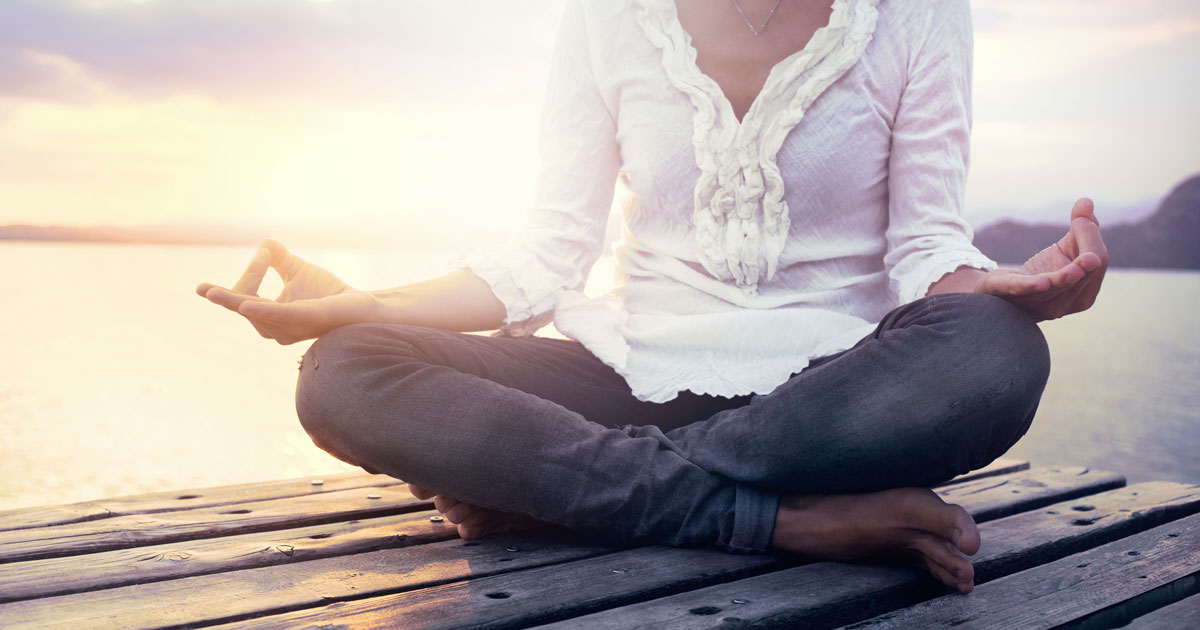 Woman sitting cross-legged on dock, meditating