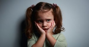 Little girl looking scared, with hands pressed to face