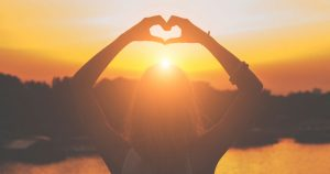 Woman standing in front of lake and sunset making heart with her hands over her head