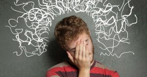 Man with hand over face, squiggly lines drawn on blackboard behind