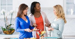 Three women standing in kitchen, talking