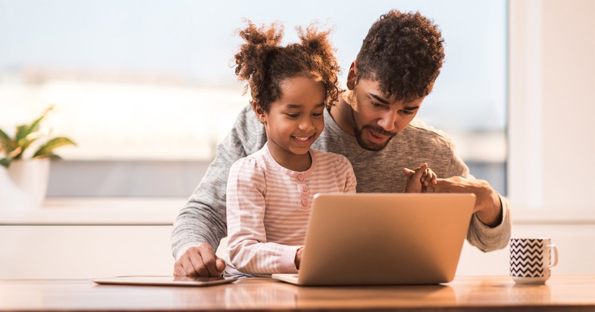 Man with daughter looking at laptop screen