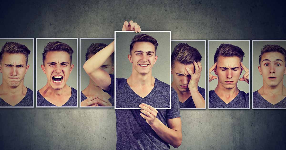 Man holding up photo of his face with other photos in line of different emotions
