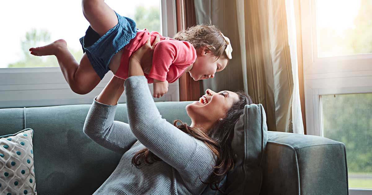 Mother playing with daughter, lifting her in the air