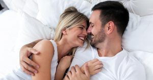 Man and woman lying in bed with arms around each other