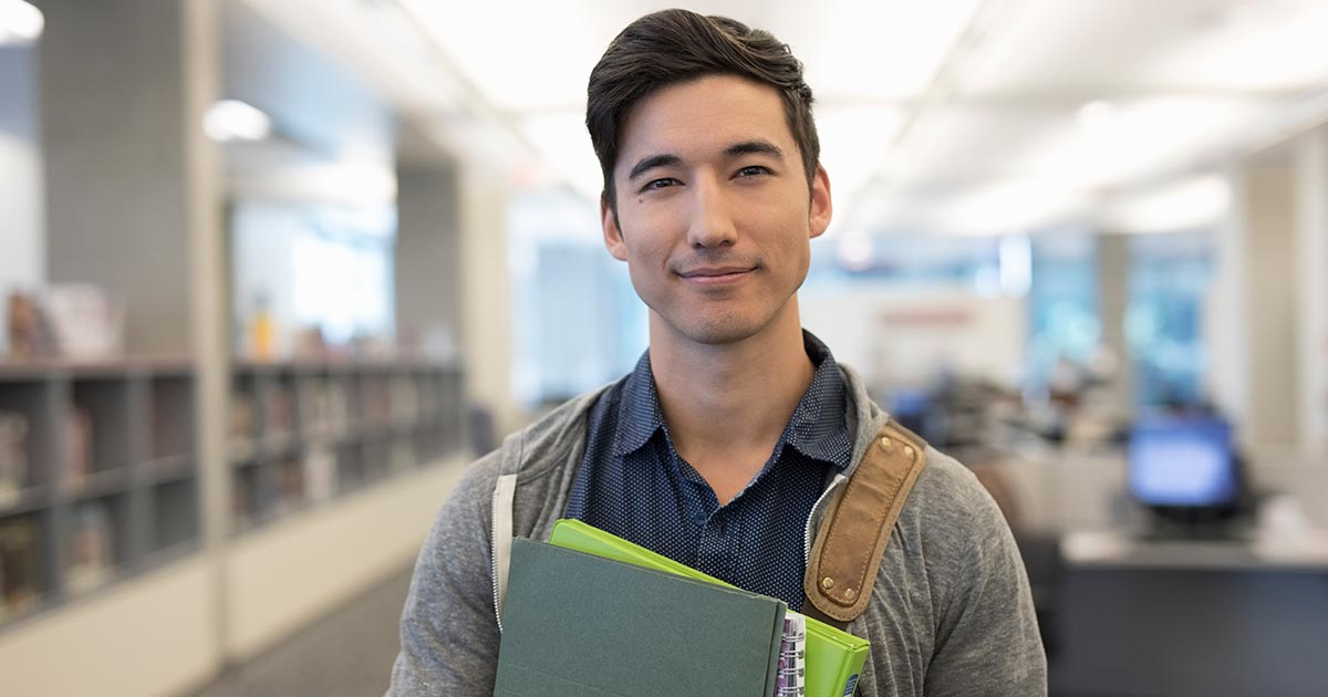 Portrait smiling, confident male college student in library