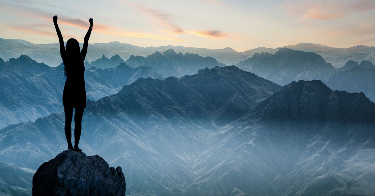 a person with lots of motivation, standing on top of a mountain, celebrating a victory