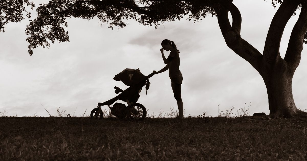 a woman at the park with a stroller, experiencing the effects of postpartum depression