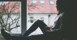 an isolated woman sitting by the window, feeling hopelessness, which is one of the common depressive bipolar symptoms in women