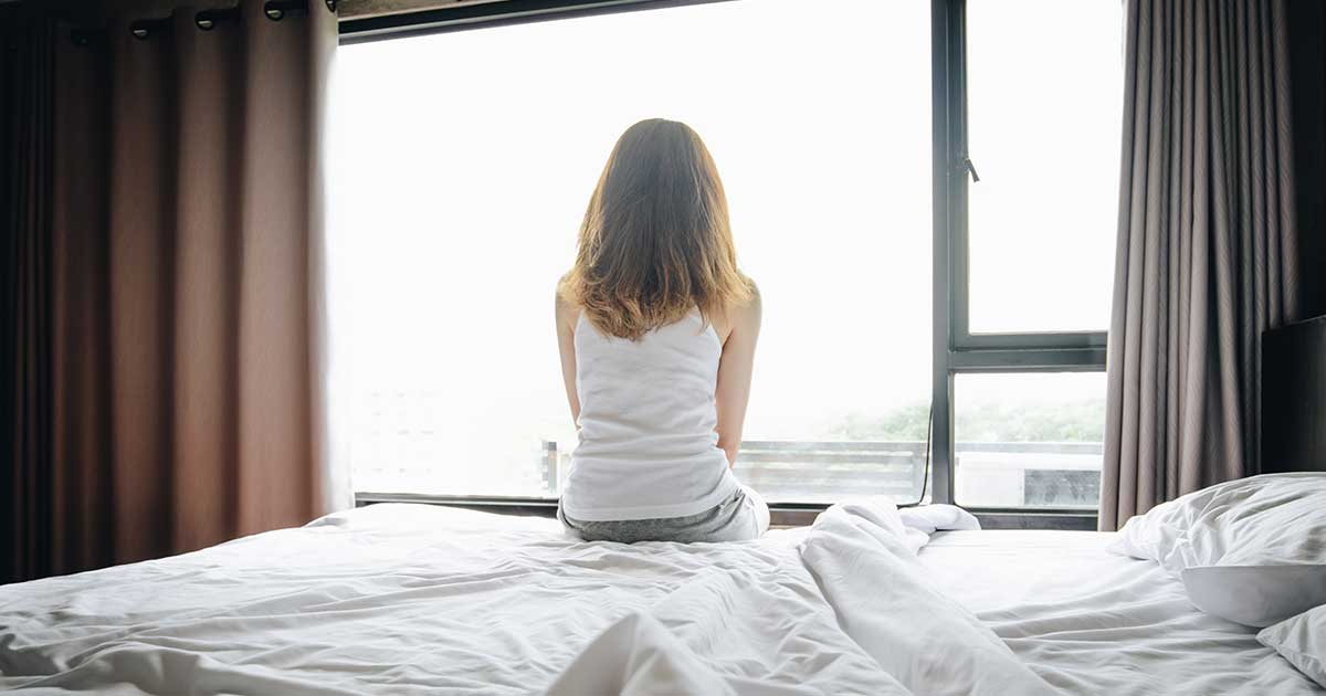 an isolated woman sitting on her bed facing the window, experiencing a depressive episode