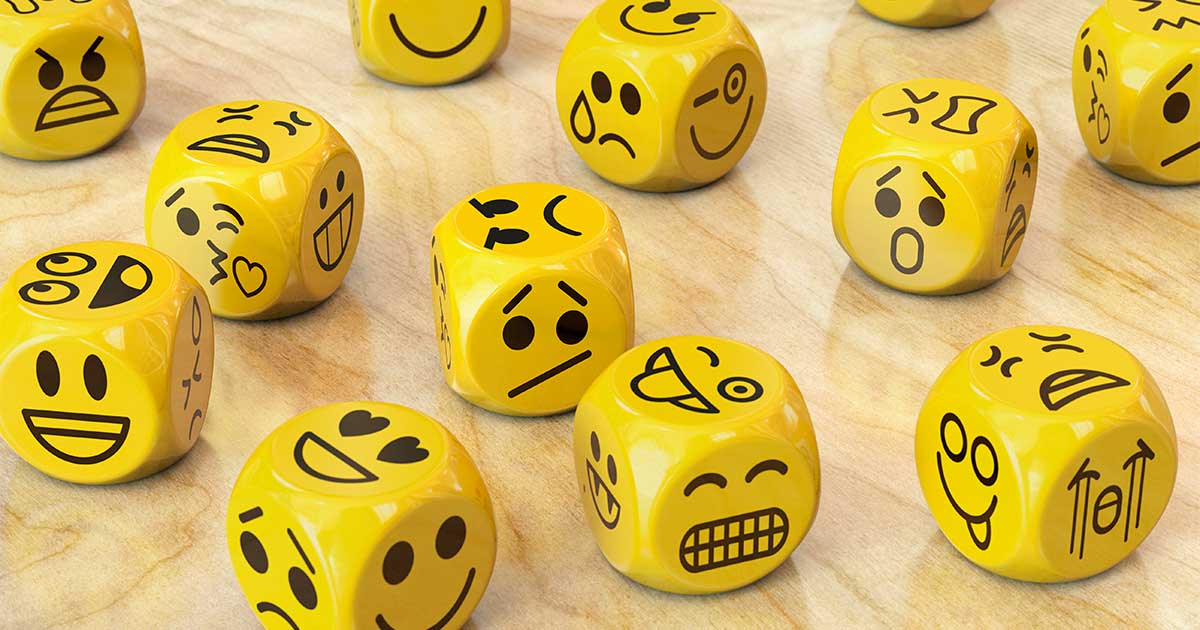 Yellow dice painted with faces of emotions.